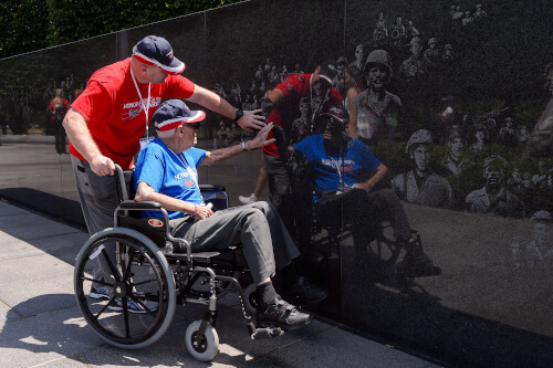 Honor Flight Veteran with Guardian next to American Flag