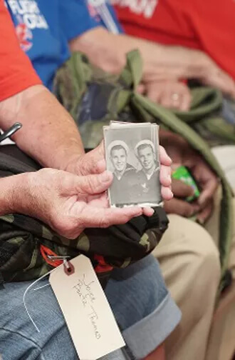 Someone showing old photos of Veterans when they were younger